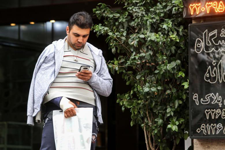 رجل ينظر لهاتفه في طهران