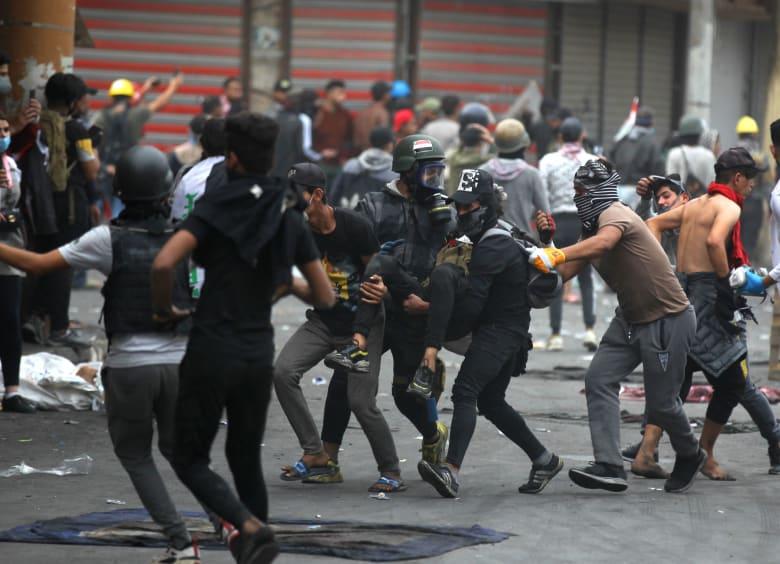 محتجون عراقيون يحملون أحد المصابين خلال الاشتباكات مع قوات الأمن