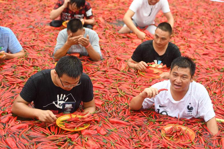 أشخاص يقفون في بركة مغطاة بالفلفل الحار أثناء مسابقة لتناوله في نينغشيانغ بمقاطعة هونان الصينية