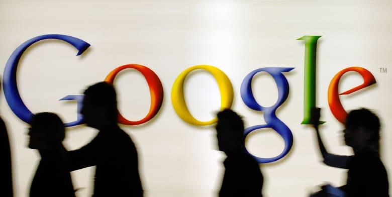 أشخاص يمشون خلف شعار محرك البحث على الإنترنت غوغل في دوسلدورف