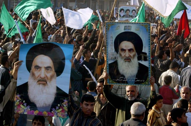 متظاهرون عراقيون يرفعون صور المرجع الشعي الأعلى آية الله علي السيستاني