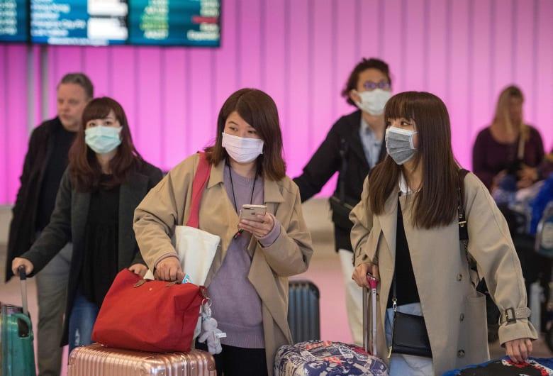 مسافرون في مطار لوس أنجلوس يرتدون أقنعة طبية بعد اكتشاف إصابات بفيروس كورونا الجديد