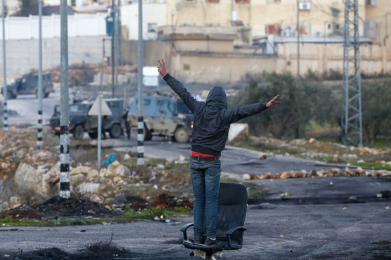 متظاهر فلسطيني مقابل قوات الأمن الإسرائيلية خلال الاشتباكات عقب مظاهرة احتجاج على اقتراح خطة سلام أمريكية