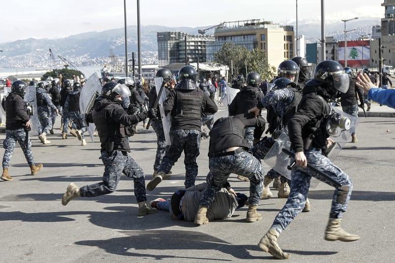 شرطة مكافحة الشغب اللبنانية تلاحق أحد المتظاهرين المعارضين للحكومة خلال اشتباكات في مظاهرة في وسط العاصمة اللبنانية بيروت