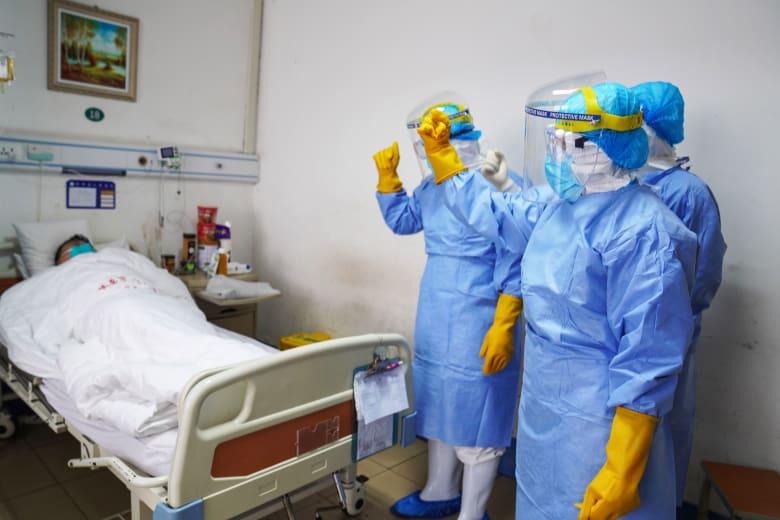 أفراد طاقم طبي في الصين بغرفة مُصاب بفيروس كورونا