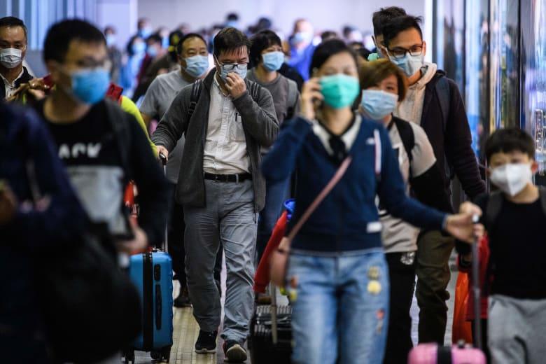 صورة ارشيفية لمسافرين يرتدون أقنعة في الصين