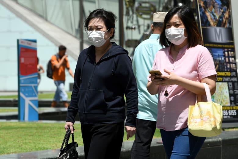 سيدتان في سنغافورا ترتديان أقنعة للوقاية من فيروس كورونا الجديد