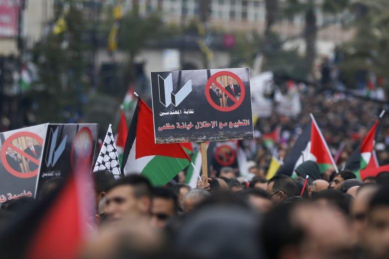 متظاهر فلسطيني يحمل لافتة مناهضة لتطبيع العلاقات مع اسرائيل في مدينة رام الله بالضفة الغربية
