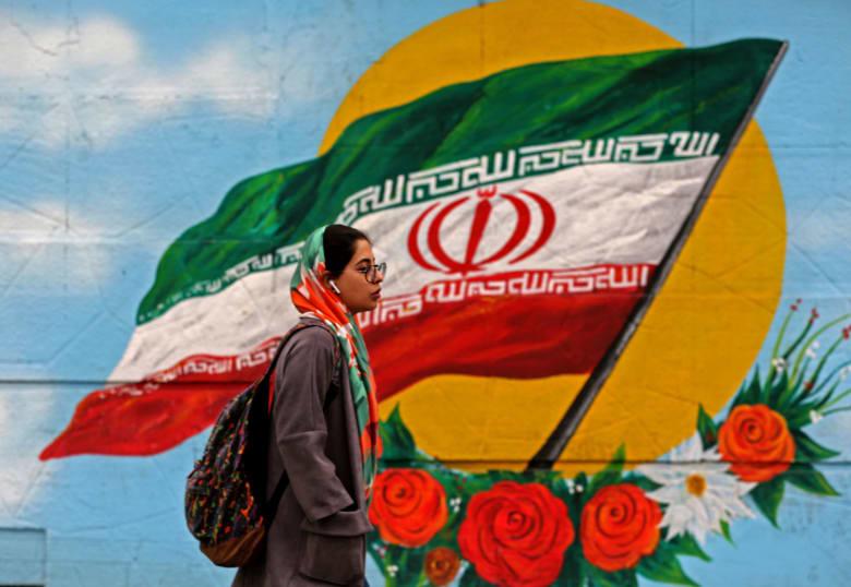 صورة ارشيفية لفتاة تمر من أمام رسمة للعلم الإيراني في طهران