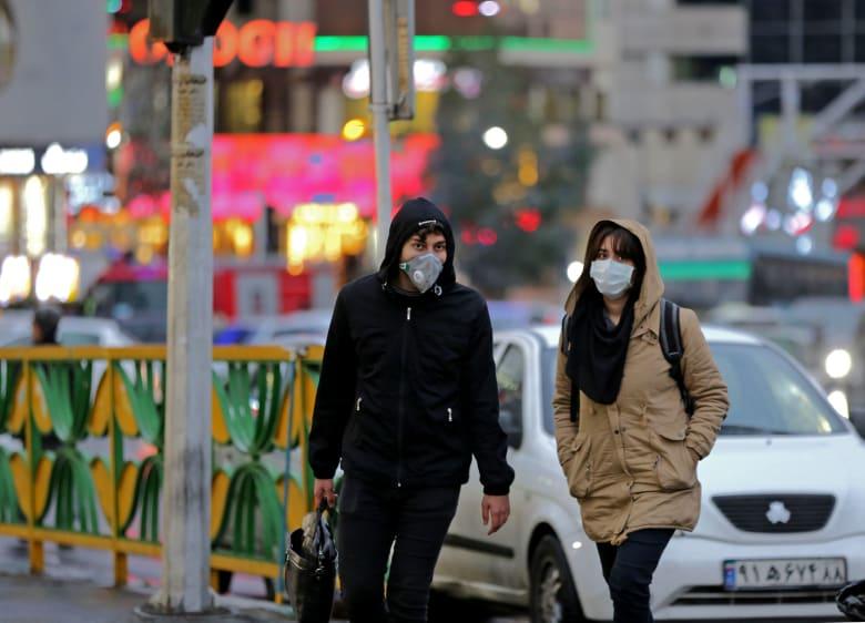 إيرانيتان ترتديان أقنعة طبية واقية بعد اكتشاف عدد من الإصابات بقيروس كورونا