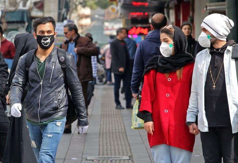 إيرانيون يرتدون أقنعة طبية واقية بعد انتشار فيروس كورونا في البلاد