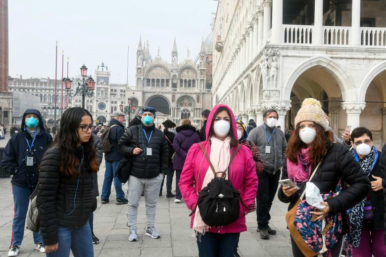 سياح في مدينة فينيسيا الإيطالية يرتدون أقنعة واقية بعد انتشار فيروس كورونا في عدة مدن بالبلاد