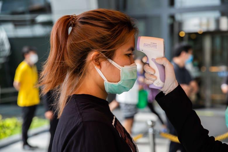 موظفو صحة يرتدون أقنعة الوجه يفحصون الناس عند دخولهم إلى بورصة تايلاند في 28 فبراير 2020 في بانكوك ، تايلاند.