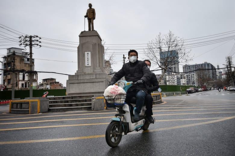 رجل يرتدي قناعًا طبيًا واقيًا في مدينة ووهان الصينية التي تفشى فيها فيروس كورونا