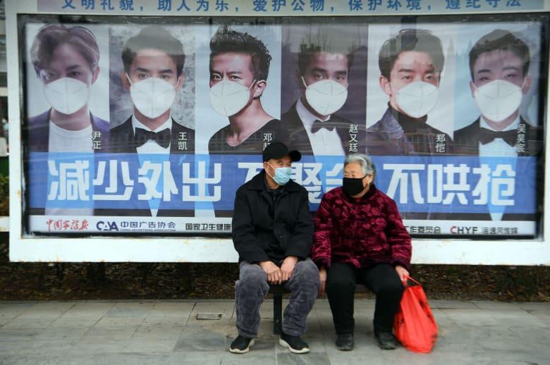 سيدة ورجل أمام إحدى لافتات حول ارتداء الأقنعة الطبية بعد تفشي فيروس كورونا في الصين
