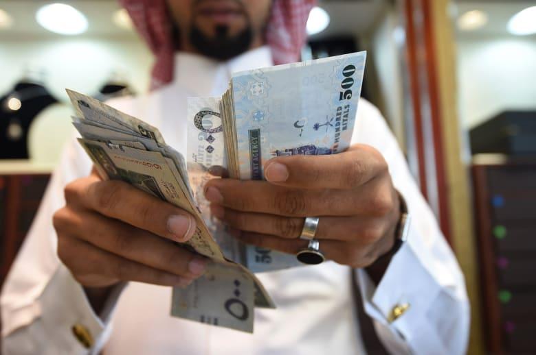 صورة أرشيفية لرجل يمسك بأوراق من فئة 500 ريال سعودي