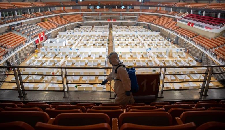 عامل يعمل على تعقيم إحدى المستشفيات المقامة في ملعب رياضي في الصين