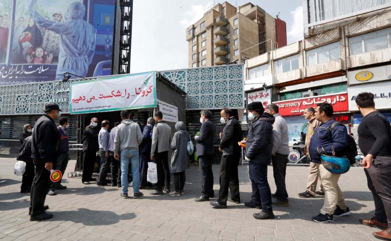 إيرانيون يصطفون لتلقي مساعدات طبية للوقاية من فيروس كورونا المستجد الذي تفشى في البلاد