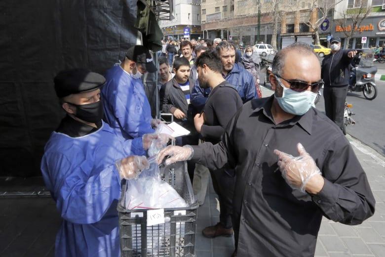 إيرانيون يتلقون مساعدات طبية للوقاية من فيروس كورونا المستجد الذي تفشى في البلاد