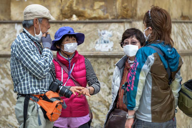 سائحون يرتدون أقنعة طبية للوقاية من فيروس كورونا في أحد الأماكن الأثرية في مصر