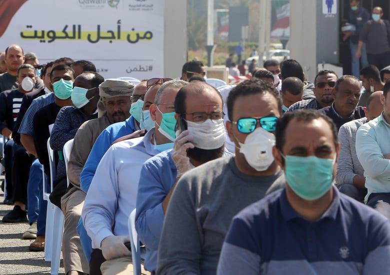 عدد من المسافرين إلى الكويت من عدة دول في انتظار إجراءات الكشف الطبي بعد انتشار فيروس كورونا