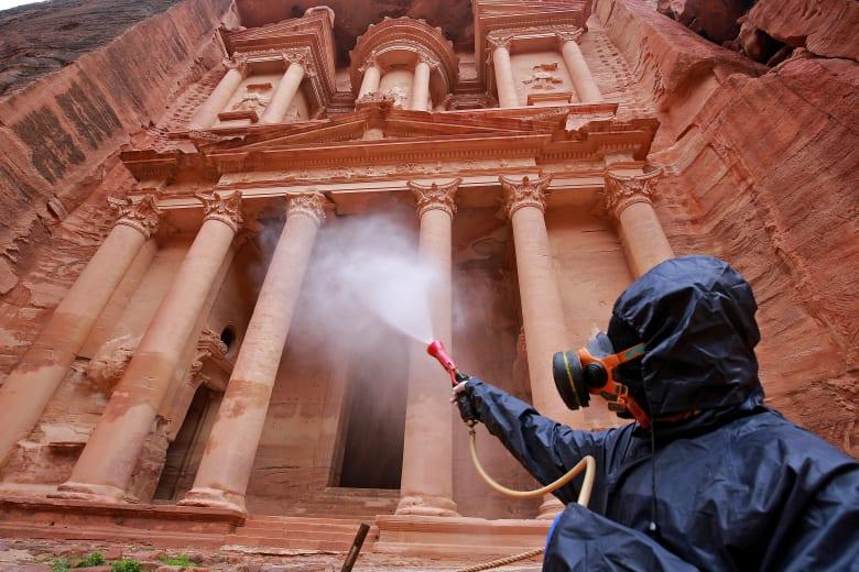 عامل يقوم بتعقيم موقع البتراء الأثري في الأردن بعد انتشار فيروس كورونا