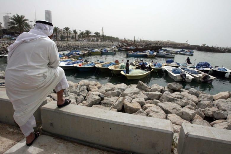 صورة ارشيفة لرجل ينظر غلى عمال وافدين في الكويت