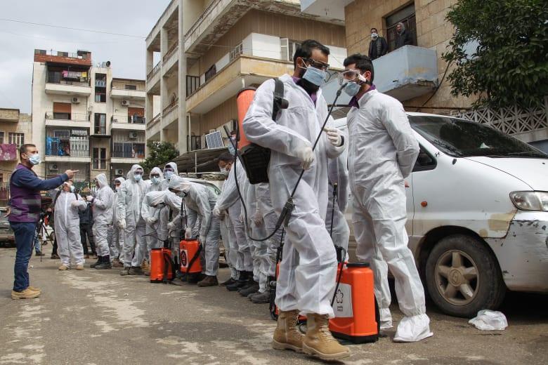 متطوعون سوريون يعملون على تعقيم الأماكن العامة في إدلب شمال غرب سوريا