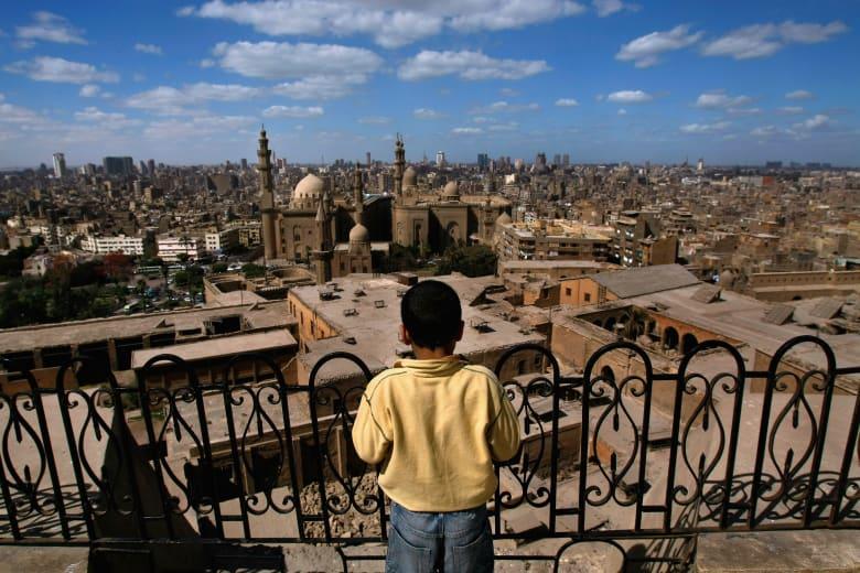 صورة أرشيفية لطفل ينظر إلى مسجد من شرفة في مصر
