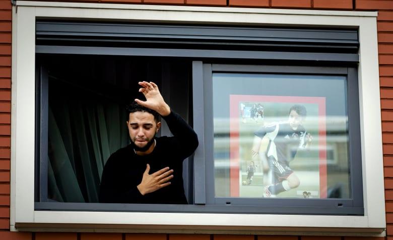 صورة أرشيفية لشقيق عبدالحق نوري يلوح لمؤيدين حضروا خارج منزله لتقديم الدعم بعد إصابة لاعب أياكس العام 2017