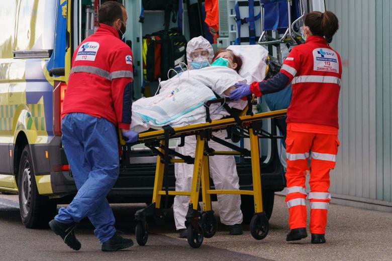 عمال طبيون ينقلون إحدى المصابات بفيروس كورونا المستجد في إسبانيا