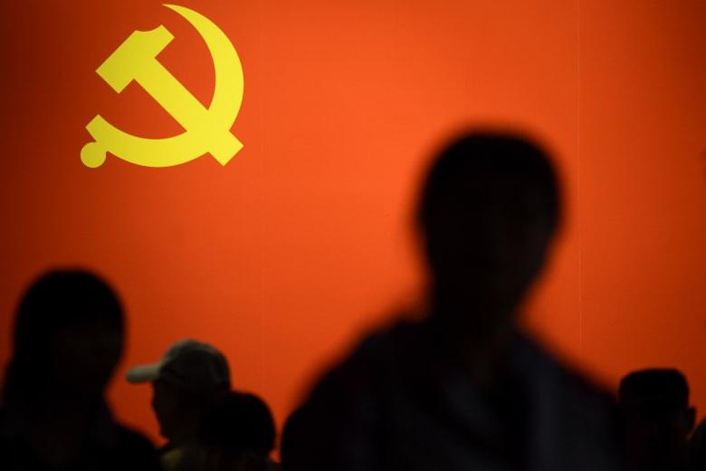صورة أرشيفية لأشخاص يمرون أمام راية الحزب الشيوعي في الصين