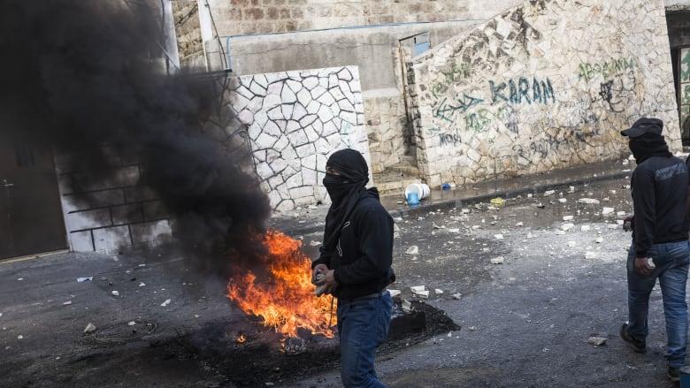 النيران تشتعل في أحد الإطارات قرب شاب فلسطيني بالقدس خلال مواجهات مع القوات الإسرائيلية.