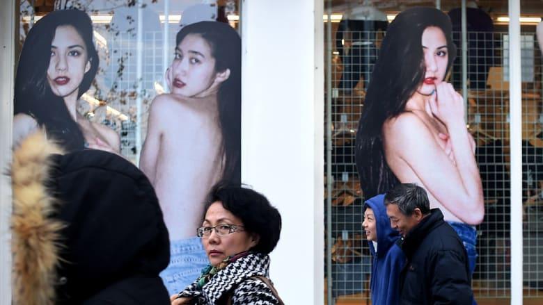 صينيون يمرون أمام فاترينات عرض بمحلات بعد الكشف عن تباطؤ نمو الاقتصاد للشهر الـثامن على التوالي