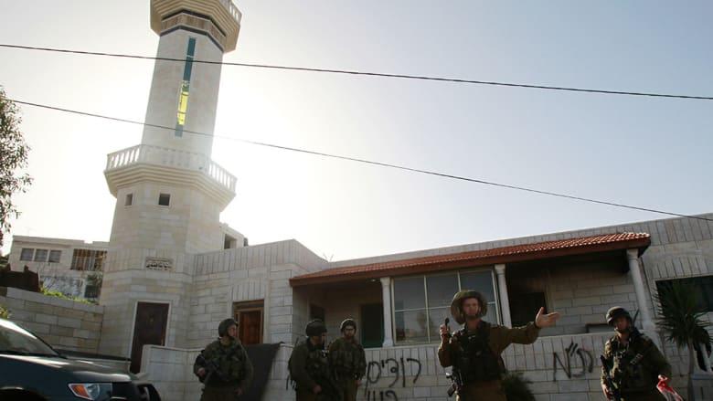 جنود إسرائيليون يطوقون المسجد الذي أحرق قرب بيت لحم.