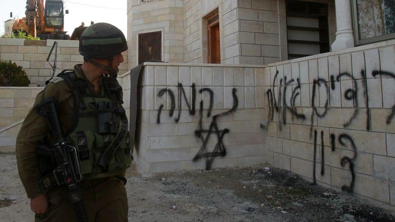 جندي إسرائيلي ينظر باتجاه عبارات مسيئة للعرب كتبت على جدران المسجد قرب بيت لحم.