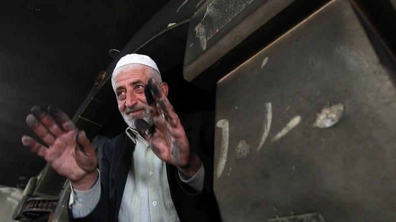إمام المسجد يرفع يديه أمام عدسات المصورين لعرض آثار الرماد.