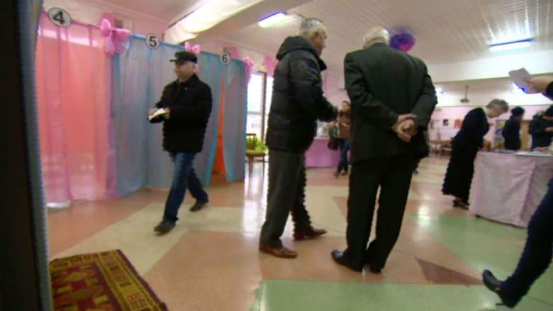 شخص يدلي بورقتي تصويت في استفتاء القرم