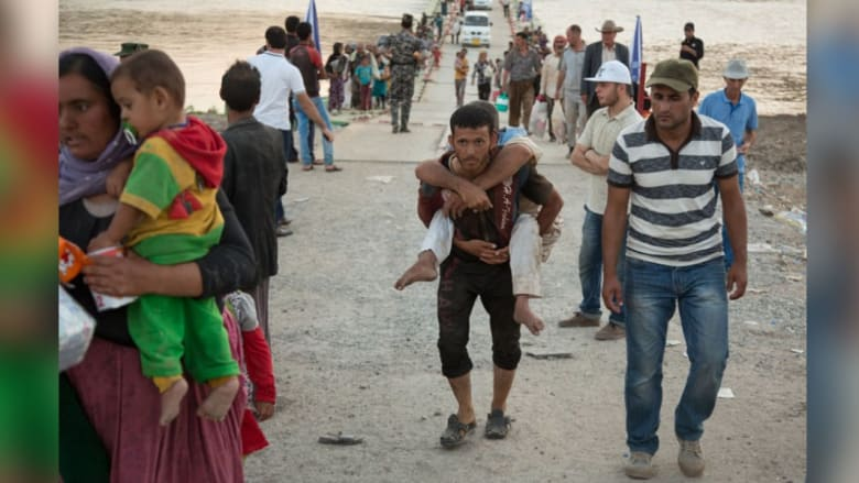 لاجيء عراقي يحمل مقعدا مسنا