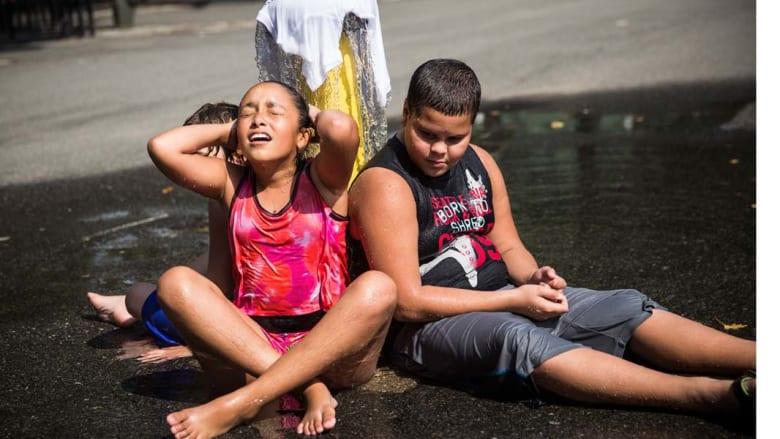 نيويورك، الولايات المتحدة-- طفلان يبتردان بجانب نافورة للمياه في نيويورك في ظل صيف حار تشهده المدينة 2 سبتمبر/ أيلول 2014