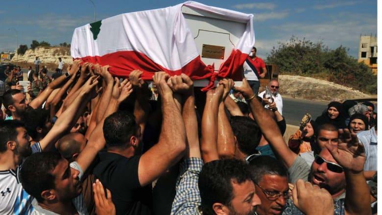 """القملون، لبنان -- لبنانيون من الطائفة السنية يشعيون جثمان الجندي علي سيد ملفوفة بالعلم اللبناني في قرية القلمون إلى الجنوب من طرابلس الذي أعلن """"الجهاديون"""" عن قطع رأسه عرسال - 3 سبتبمبر/ أيلول 2014"""