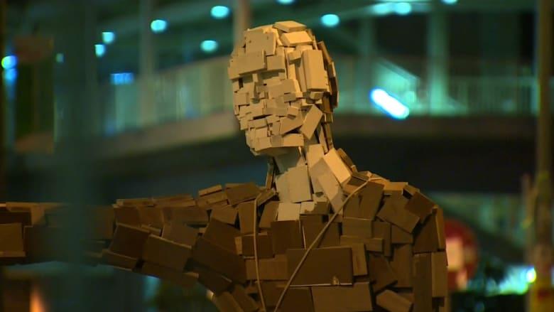 طريقة صينية سلمية للتعبير.. تمثال خشبي لرجل يحمل مظلة