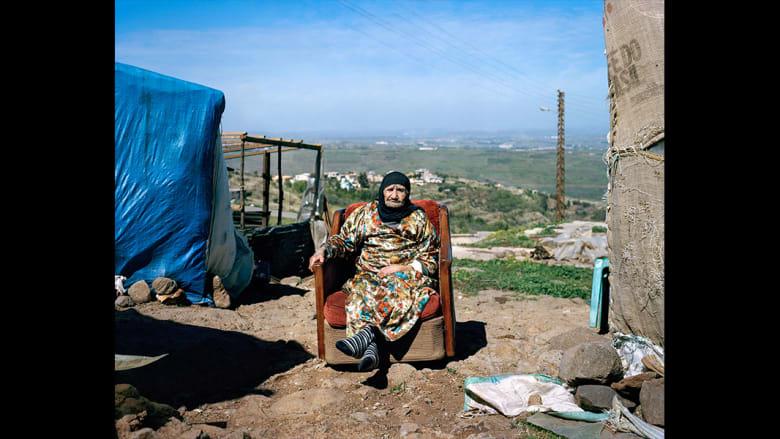 دغّة، تبلغ 101 عاما، تعمل على الملابس وهي تستمع لأصوات سقوط القذائف على سوريا من مأوى أسرتها في شمال لبنان.
