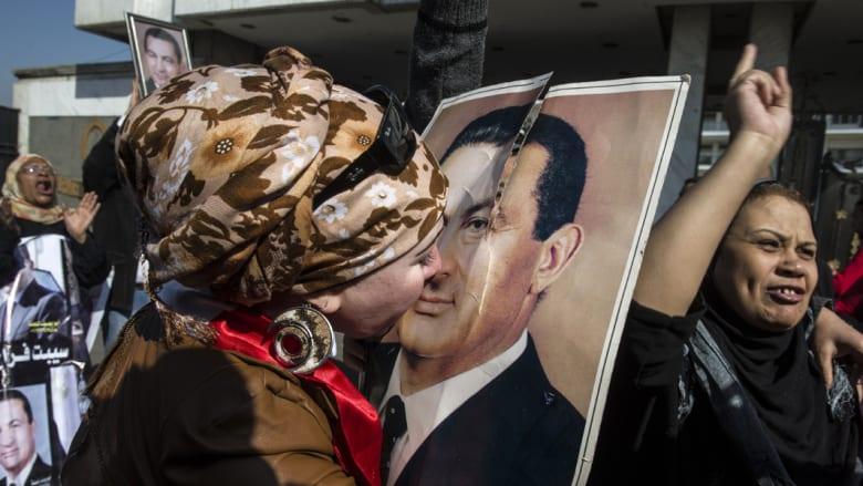 مصرية من أنصار مبارك تقبل صورة له بعد إعلان قرار البراءة