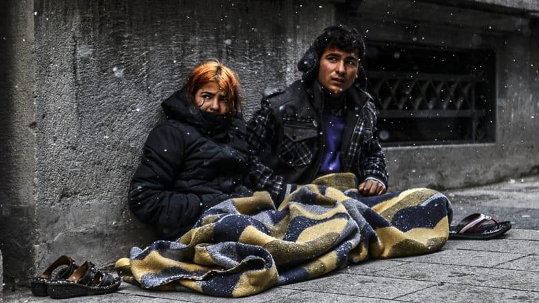 لاجئون سوريون يجلسون على الرصيف تحت الثلوج في اسطنبول