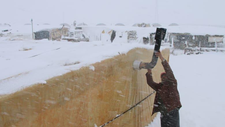 عامل يثبت أنبوب مدفأة على الوقود يستخدمها اللاجئون السوريون في مخيم غير رسمي بلبنان