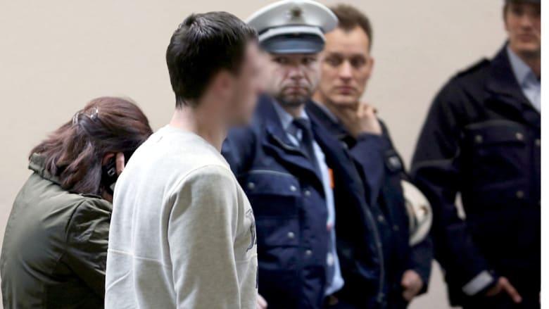 ضابط شرطة يقتاد أقارب الضحايا إلى المنطقة المخصصة لهم في مطار دوسلدورف بألمانيا