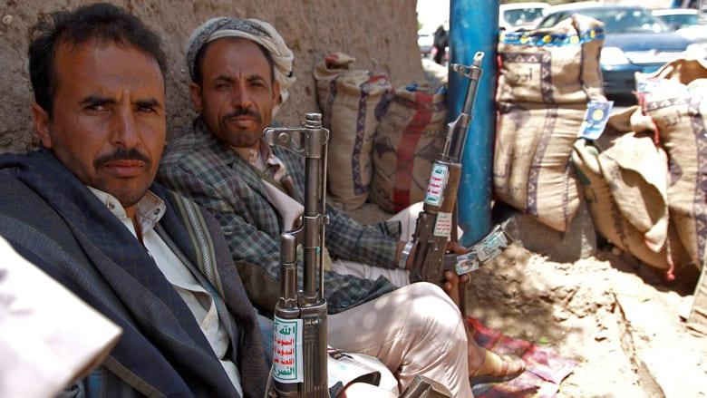 عدد من أنصار جماعة الحوثيين يحملون البنادق ويجلسون على قارعة الطريق في صنعاء.