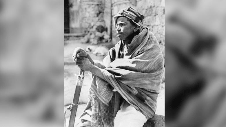 شاب بدوي مسلح بسيف يعمل في مراقبة الأمن في أحد شوارع جدة 1930