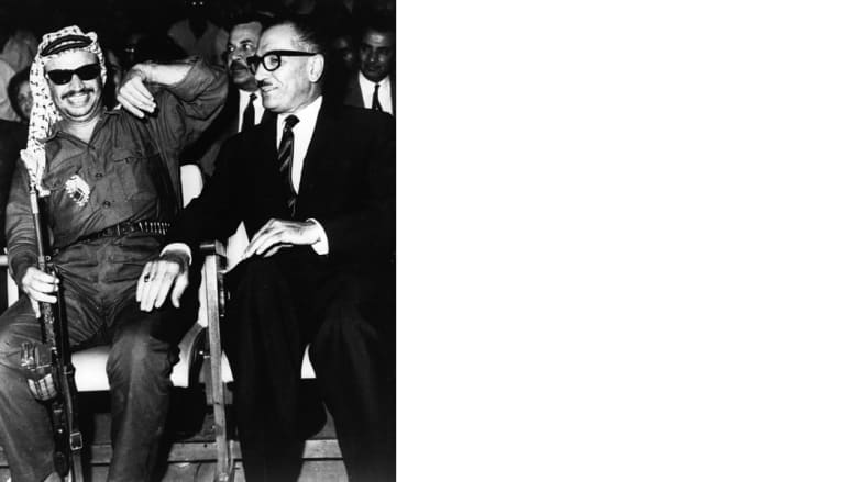 رئيس السلطة الوطنية الفلسطينية ياسر عرفات (يسار) يظهر وهو يحمل بندقية، وإلى اليمين رئيس وزراء الأردن عبدالمنعم الرفاعي، عمان الأردن، 12 أغسطس/ آب 1969